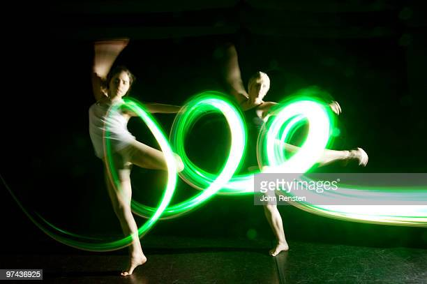 coordinated dancers in green abstract light trail