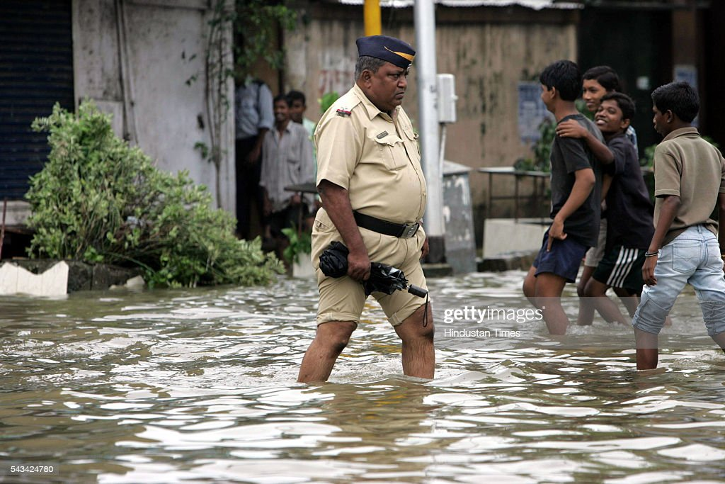 A cop pulled up his pant to save it from the water logged at Naigaum at July 31, 2005 in Mumbai, India.