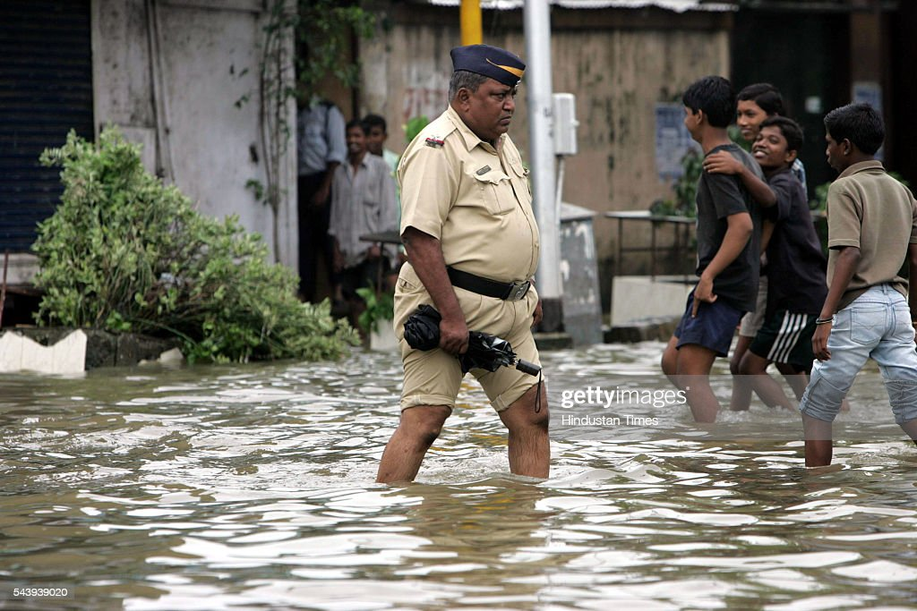 A cop pulled up his pant to save it from the water logged at Naigaum on July 31, 2005 in Mumbai, India.