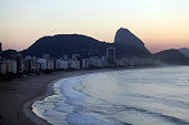 Copacabana beach one of the world's most famous urban beaches at sunrise with Sugar Loaf Mountain in the distance The beach and hotel strip stretches...