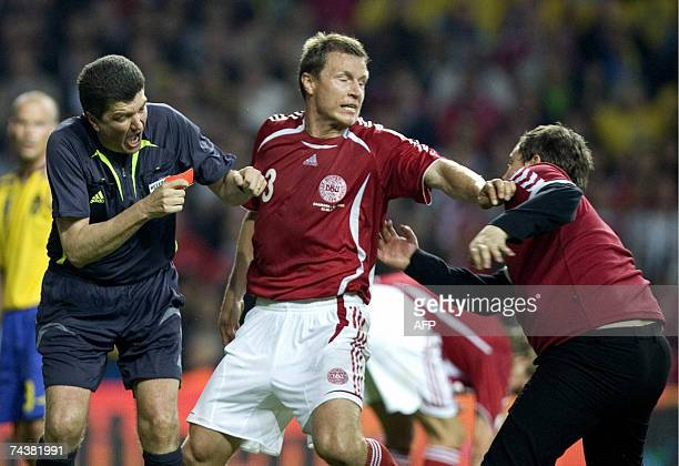Denmark's Michael Gravgaard tries to intervene as a Danish supporter attacks referee Herbert Fandel for giving Sweden a late penalty during the Euro...