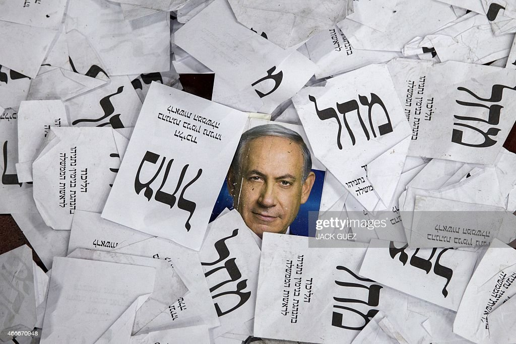 Copies of ballots papers and campaign posters for Israel's Prime Minister Benjamin Netanyahu's Likud Party lie on the ground in the aftermath of the...