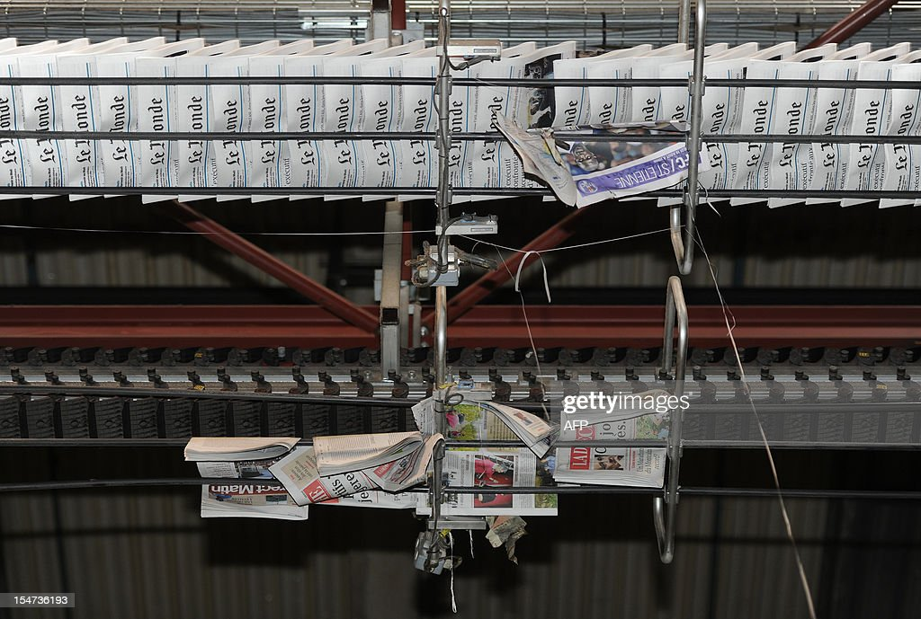 Copies of French daily newspaper 'Le Monde' are pictured in the printing house of 'La Depeche du Midi', the southwestern newspaper on October 25, 2012 in Toulouse. Part of the Le Monde newspaper production is now printed in Toulouse and is now available in the city at midday instead of the following morning. AFP PHOTO / ERIC CABANIS