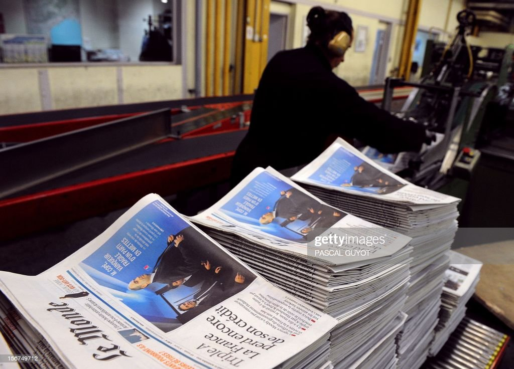 Copies of French daily newspaper 'Le Monde' are pictured in the printing house of 'Le Midi Libre', the southwestern newspaper on November 20, 2012 in Saint Jean de Vedas. Part of the Le Monde newspaper production is now printed in Saint-Jean-de-Vedas, near the southern city of Montpellier and is now available in the city at midday instead of the following morning. AFP PHOTO / PASCAL GUYOT