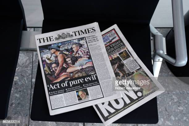Copies of the English tabloid newspapers The Times and The Sun are left on a seat in the terminal at Heathrow International Airport in London England...