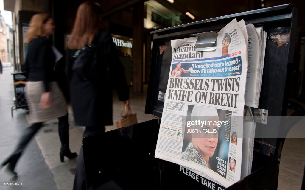 Copies of the Evening Standard newspaper, on the day that Britain's former Chancellor of the Exchequer, George Osborne, took over as editor, are pictured outside St James's Park underground station in London on May 2, 2017. When his appointment was announced, Osborne, 45, said he was 'thrilled' to take on the job and wanted to make the daily 'the definitive voice of the world's most exciting city'. / AFP PHOTO / Justin TALLIS