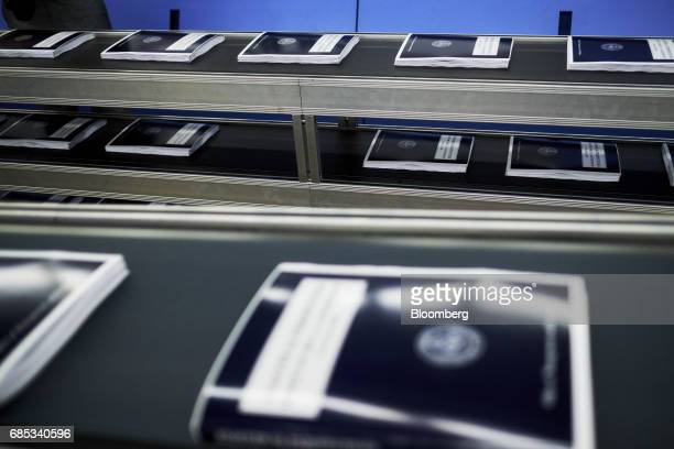 Copies of the fiscal year 2018 budget move along a conveyor belt during the binding process inside the Government Publishing Office production...