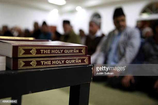 Copies of the Quran sit on a table as Muslim men pray in the mosque during a prayer vigil at Baitul Hameed Mosque on December 3 2015 in Chino...