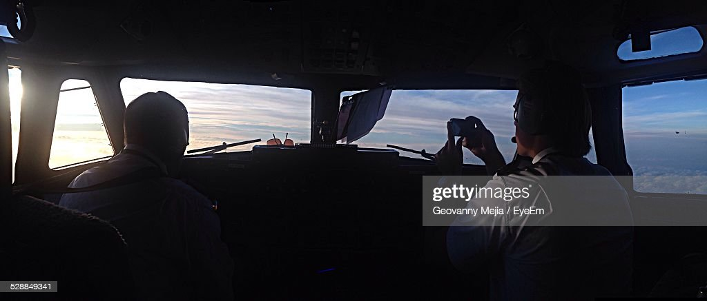 Co-Pilot Taking Picture Of Sunset In Cockpit