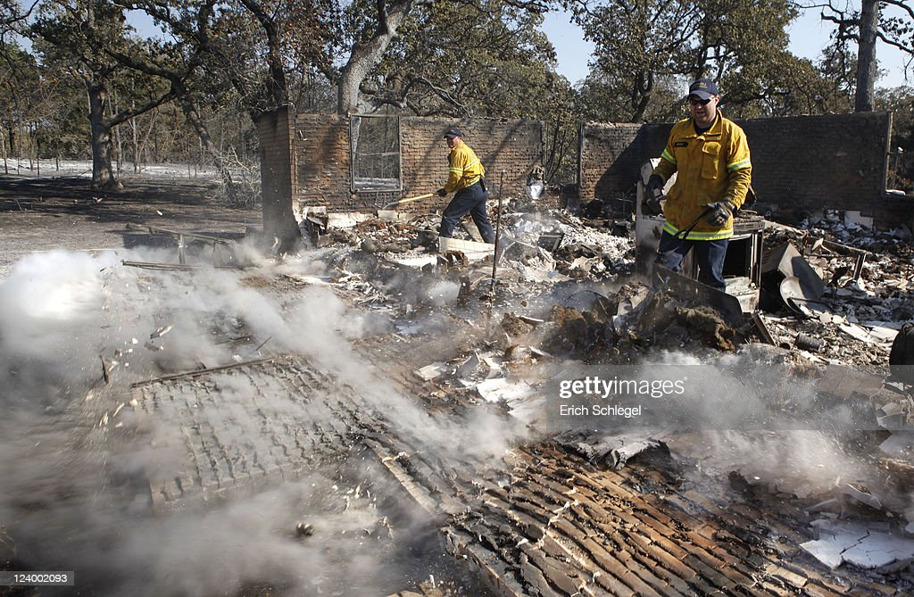 Coppell Fire Department firefighters knock down a house wall as they hit hot spots in the wildfire affected areas September 7, 2011 around Bastrop, Texas. Several large wildfires have been devastating Bastrop County for the last three days, but are now 30 percent contained, according to the Texas Forest Service.