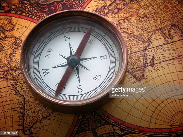 Copper compass on antique world map