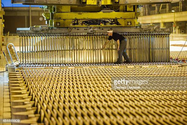 Copper tankhouse of Aurubis AG which produces copper cathodes from the copper anodes an employee uses a crane to fill electrolysis baths with copper...