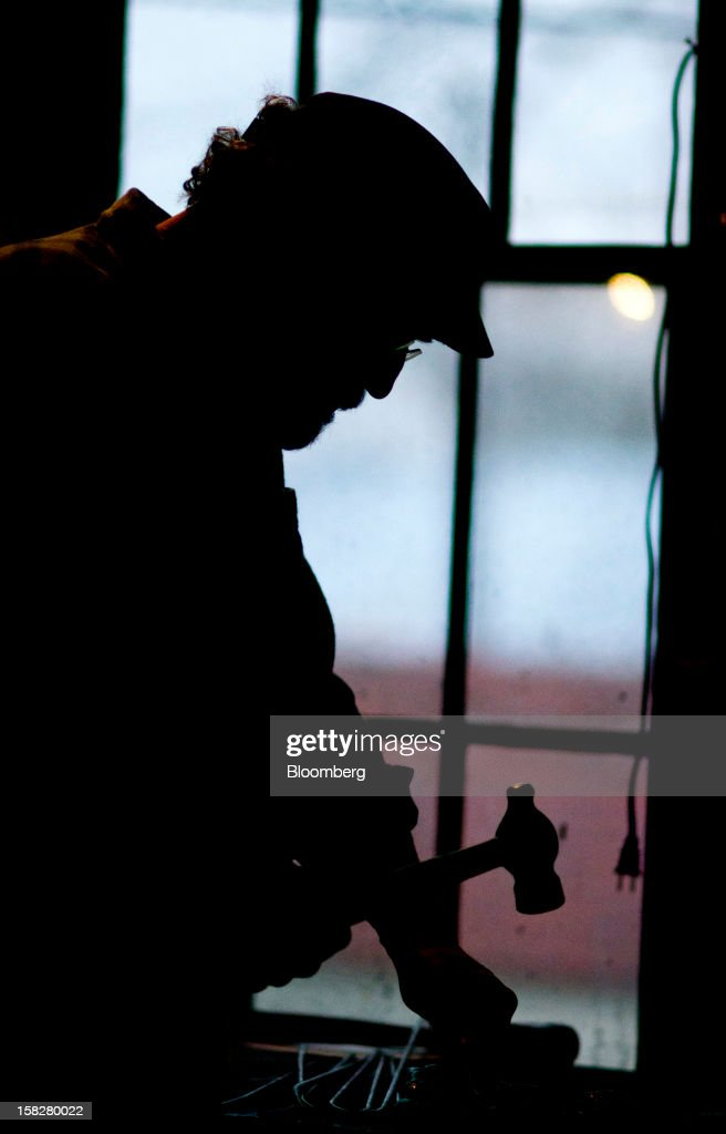 Coppersmith Steve Shiffer is silhouetted as he works in the fabrication area at the D Picking & Co. facility in Bucyrus, Ohio, U.S., on Tuesday, Dec. 11, 2012. Copper rose on bets that moves by the Federal Reserve to expand economic stimulus will weaken the dollar and boost demand in the U.S., the world's second-largest user of the metal. Photographer: Ty Wright/Bloomberg via Getty Images