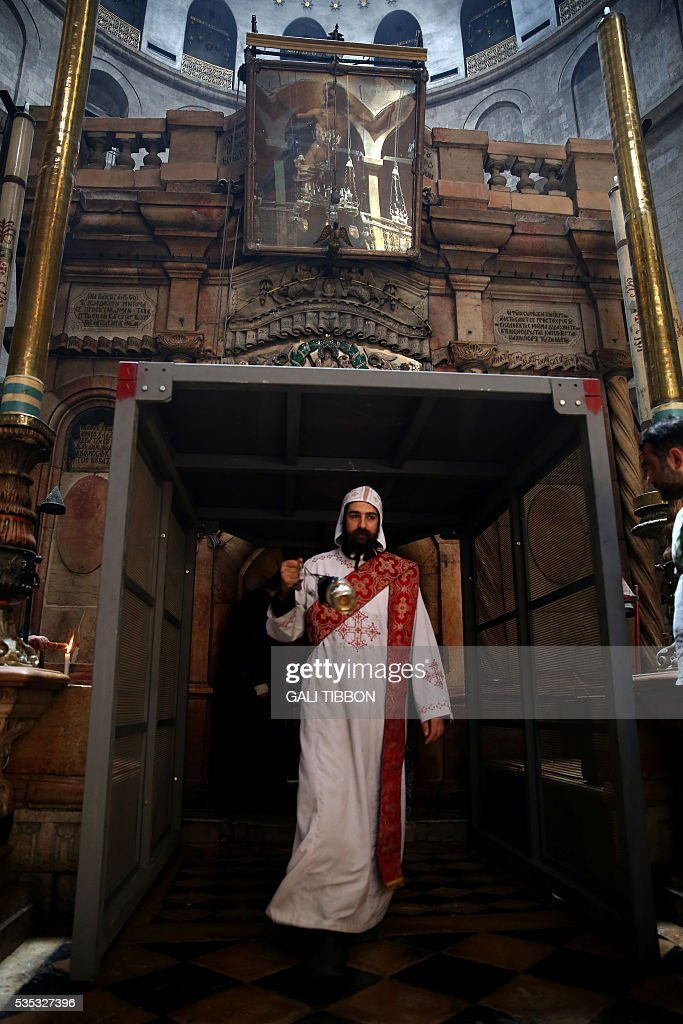 A Coptic monk swings incense at the entrance of the Tomb of Jesus as he walks under a metal scaffolding built at the entrance ahead of the restoration on May 29, 2016, at the Church of the Holy Sepulchre in Jerusalem's Old City. The tomb where Jesus is said to have been buried before his resurrection, is to undergo major restoration. The restoration entrusted to a Greek team, is expected to be completed in early 2017 and the site will remain open to visitors in the meantime. / AFP / GALI