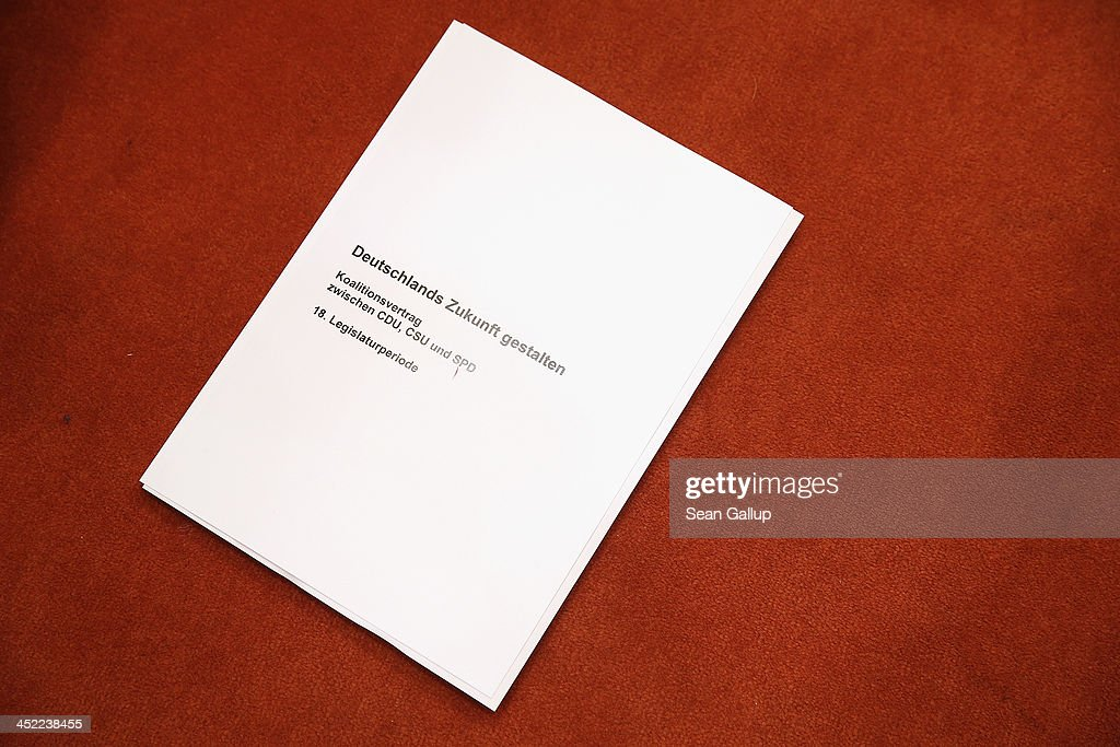 A copy of the 177-page three-party coalition contract lies on the ground shortly after German Chancellor and Chairwoman of the German Christian Democrats (CDU) Angela Merkel, Chairman of the German Social Democrats (SPD) Sigmar Gabriel and Chairman of the Bavarian Christian Democrats (CSU) Horst Seehofer spoke to the media after signing it at the Bundestag on November 27, 2013 in Berlin, Germany. The three parties worked their way through arduous negotiations on policy issues that concluded with a 17-hour overnight session last night in order to hammer out the final details that will make a new German coalition government possible. The agreement still requires approval by party delegates, which especially in the case of the SPD is uncertain.