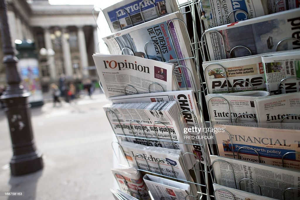 A copy of the newspaper 'L'opinion' is pictured amongst other newspapers in a newsstand on May 15, 2013 in Paris. The newspaper, also available online, was released on May 15, 2013 in France.