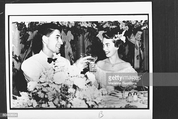 Copy photo of Dr Milton Brothers and his bride psychologist Dr Joyce Brothers sitting at their wedding reception clinking champagne glasses and...