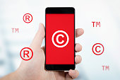 Copyright, trademark symbols flying around smartphone. Security and piracy composition