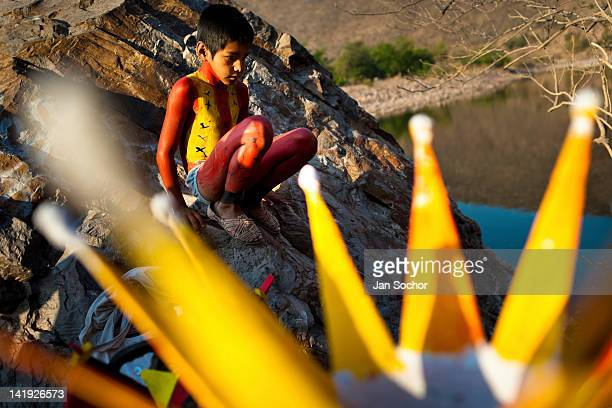 Cora Indian boy with body painted all over in red color sits on a rock before the religious ritual celebration of Semana Santa in Jesús María Nayarit...