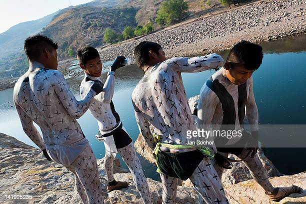 Cora Indian boys painting each other their bodies prepare themselves for the sacred ritual ceremony of Semana Santa in Jesús María Nayarit Mexico 21...