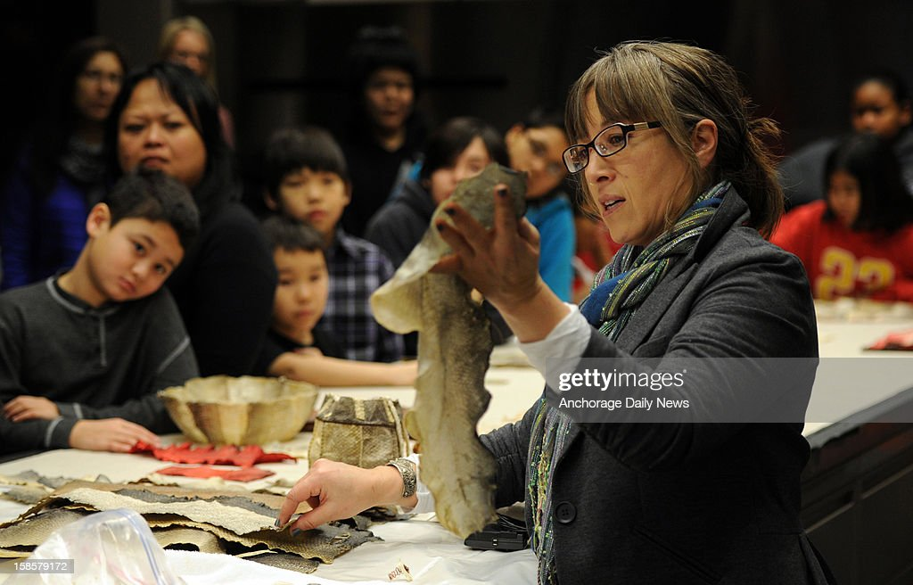 Coral Chernoff, right, of Kodiak, explains how she prepares salmon skins for sewing as students from the Alaska Native Cultural Charter School visit the Smithsonian Arctic Studies Center, December 5, 2012 in the Anchorage Museum at Rasmuson Center.