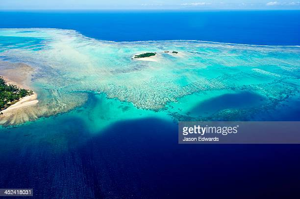 Coral reefs stretch out from the shoreline of a tropical island.