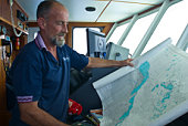 A ships captain examines a maritime map highlighting dangerous reefs.