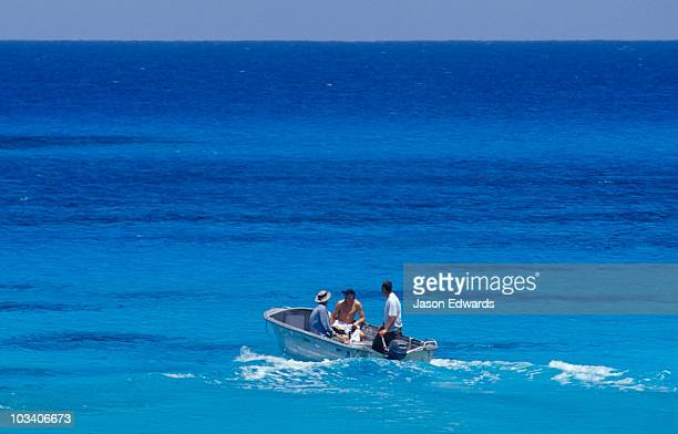 A group of men on a tropical turquoise ocean in an aluminium dingy.