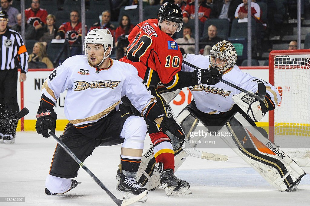 <a gi-track='captionPersonalityLinkClicked' href=/galleries/search?phrase=Corban+Knight&family=editorial&specificpeople=5944763 ng-click='$event.stopPropagation()'>Corban Knight</a> #10 of the Calgary Flames looks for an opportunity as <a gi-track='captionPersonalityLinkClicked' href=/galleries/search?phrase=Mark+Fistric&family=editorial&specificpeople=2129692 ng-click='$event.stopPropagation()'>Mark Fistric</a> #28 (L) and <a gi-track='captionPersonalityLinkClicked' href=/galleries/search?phrase=Frederik+Andersen&family=editorial&specificpeople=6605243 ng-click='$event.stopPropagation()'>Frederik Andersen</a> #31 of the Anaheim Ducks defend during an NHL game at Scotiabank Saddledome on March 12, 2014 in Calgary, Alberta, Canada. The Flames defeated the Ducks 7-2.