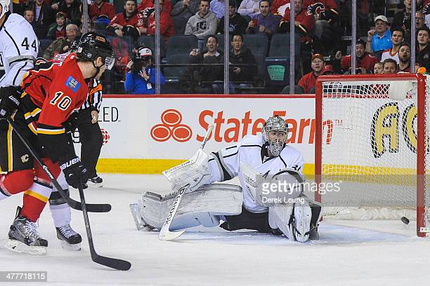Corban Knight of the Calgary Flames watches the shot of his teammate Brian McGrattan fly past the defence of Martin Jones of the Los Angeles Kings...