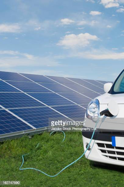 Cord from solar panels powering electric car