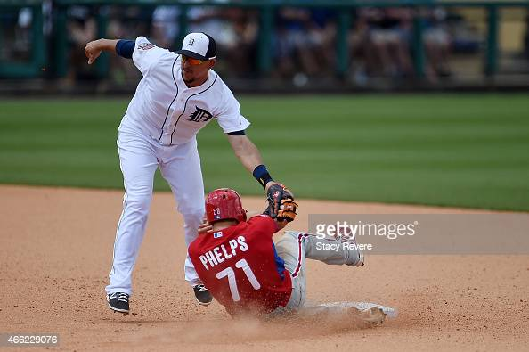 Cord Phelps of the Philadelphia Phillies is tagged out at second base by Hernan Perez of the Detroit Tigers during the fifth inning of a spring...