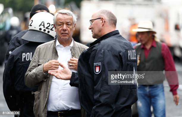 Cord Woehlke chairman of the Budnikowsky drugstore chain speaks with a policeman after one of his shops was looted during riots in Hamburg's...