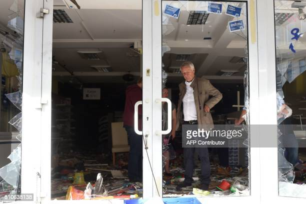 Cord Woehlke chairman of the Budnikowsky drugstore chain stands behind the broken entrance after one of his shops was looted during riots in...