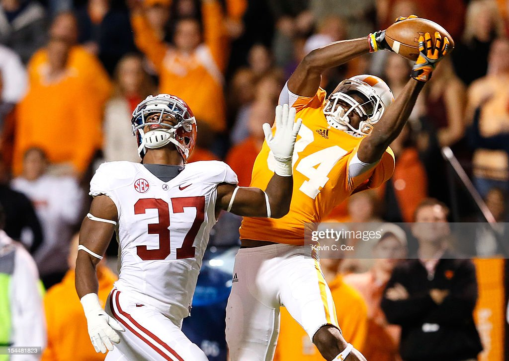Cordarrelle Patterson #84 of the Tennessee Volunteers pulls in this reception against Robert Lester #37 of the Alabama Crimson Tide at Neyland Stadium on October 20, 2012 in Knoxville, Tennessee.