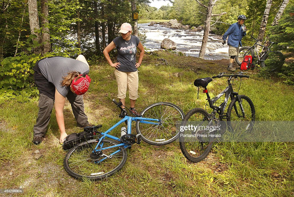 Cordell Guptill, left, and Reinelle Robinson of Mount Chase take a break at Haskell Rock Pitch while biking along the East Branch of the Penobscot River on Tuesday, July 15, 2014. At right, reporter Tux Turkel takes a drink of water.