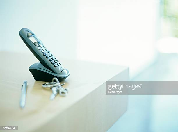 Cordless phone on table by keys and pen,differential focus