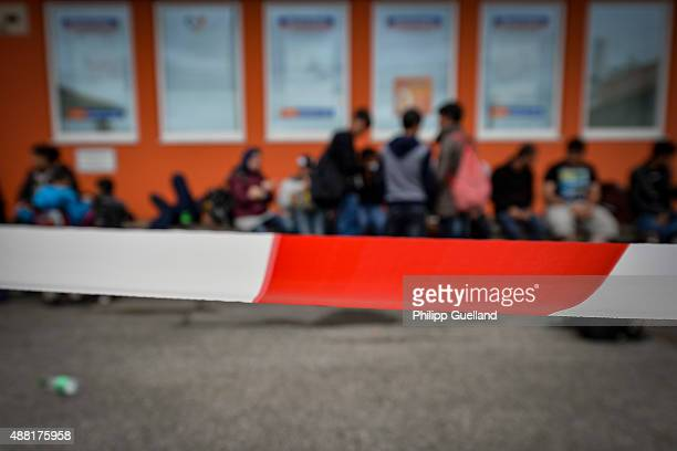 A cordon is set up in front of migrants in police custody as they wait to be brought to emergency accomodations on September 14 2015 at the railway...