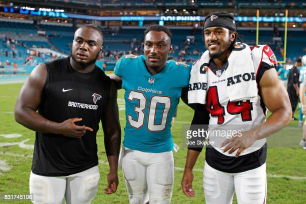 Cordrea Tankersley of the Miami Dolphins and Vic Beasley of the Atlanta Falcons walk with an unidentified Falcons player after their preseason game...