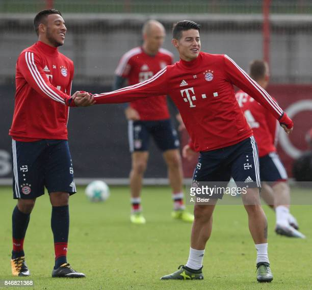 Corentin Tolisso and James Rodriguez of FC Bayern Muenchen joke during a training session at the club's Saebener Strasse training ground on September...