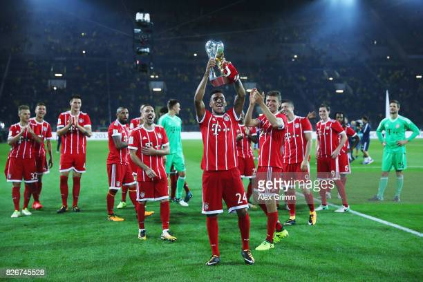 Corentin Tolisso and team mates of Muenchen celebrate with the trophy after his team won the DFL Supercup 2017 match between Borussia Dortmund and...