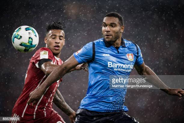 Corentin Tolisso of FC Bayern Muenchen and Jonathan Tah of Leverkusen run for the ball during the Bundesliga match between FC Bayern Muenchen and...