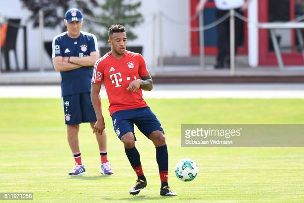 Corentin Tolisso of FC Bayern Muenchen plays the ball while head coach Carlo Ancelotti watches him during a training session at Saebener Strasse...