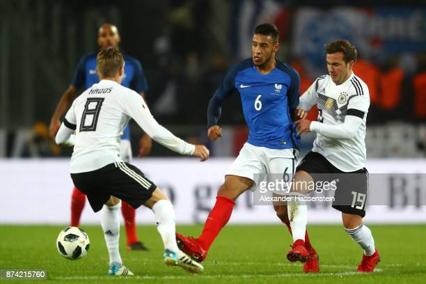 Corentin Tolisso of France and Mario Gotze of Germany battle for possession during the international friendly match between Germany and France at...