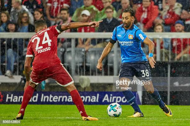 Corentin Tolisso of Muenchen and Karim Bellarabi of Leverkusen battle for the ball during the Bundesliga match between FC Bayern Muenchen and Bayer...