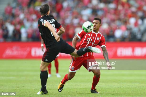 Corentin Tolisso of Muenchen battles for the ball with Riccardo Montolivo of Milan during the International Champions Cup Shenzen 2017 match between...