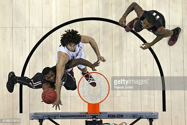 Coreontae DeBerry of the Cincinnati Bearcats attempts to shoot against Javon Baumann of the Saint Joseph's Hawks in the first half during the first...