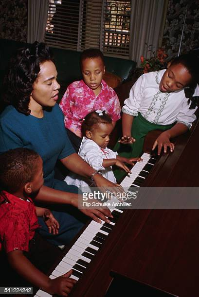 Coretta Scott King plays piano and sings with her children Yolanda Marty and Bernice at home after church