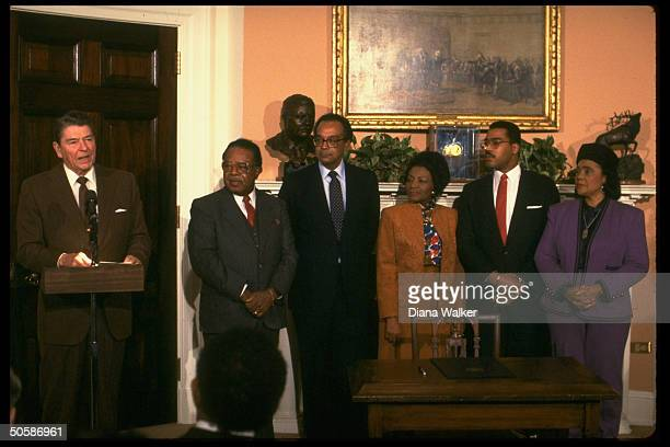 Coretta Scott King son Dexter sisterinlaw Christine Farris Pierce Abernathy President Reagan pose for photographs after proclamation of the Martin...