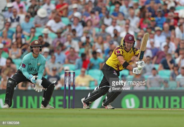 Corey Anderson of Somerset hits a boundary during his innings of 81 as Surrey wicket keeper Rory Burns looks on during the NatWest T20 Blast match at...
